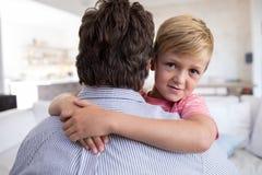 Père et fils s'embrassant dans le salon Photographie stock libre de droits