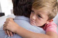 Père et fils s'embrassant dans le salon Image libre de droits