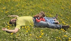 Père et fils se reposant sur un pré photographie stock libre de droits