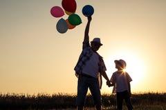 Père et fils se tenant sur la route au temps de coucher du soleil Image stock