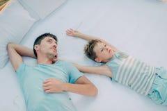 Père et fils se trouvant sur le lit Photo libre de droits
