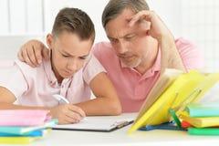 Père et fils se trouvant sur le plancher Photographie stock
