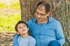 Père et fils sous un arbre en été Image libre de droits
