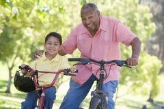 Père et fils sur des vélos souriant à l'extérieur Photographie stock