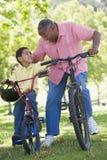 Père et fils sur des vélos souriant à l'extérieur Photo stock