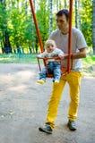 Père et fils sur une oscillation en parc images libres de droits