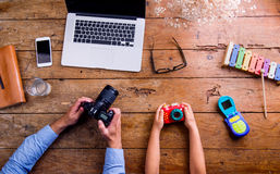 Père et fils tenant des appareils-photo, vieux bureau en bois Photo libre de droits