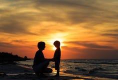 Père et fils tenant des mains au coucher du soleil Image stock