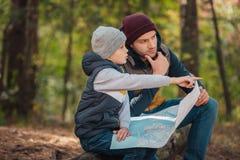 père et fils tenant la carte et se dirigeant loin avec le doigt photo stock