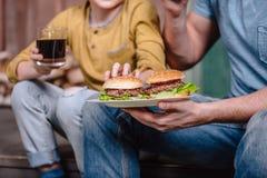 Père et fils tenant le plat avec les hamburgers faits maison photos stock