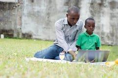 Père et fils travaillant sur un ordinateur dehors photos libres de droits