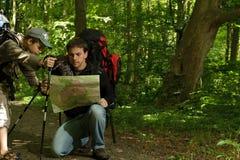 Père et fils trimardant dans la forêt Photographie stock