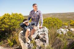 Père et fils trimardant dans les montagnes Images stock