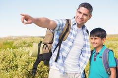 Père et fils trimardant dans les montagnes Image libre de droits