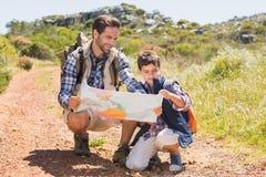 Père et fils trimardant dans les montagnes Photographie stock
