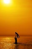 Père et fils vers la mer au coucher du soleil Photos stock