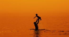 Père et fils vers la mer au coucher du soleil Photographie stock libre de droits