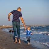 Père et fils vers la mer au coucher du soleil Photo stock