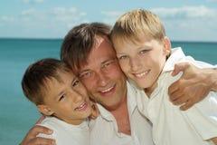 Père et garçons en mer Image stock