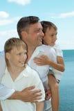 Père et garçons en mer Photos stock