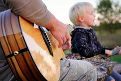 Père et guitare jouante extérieure et chant de fils Photos libres de droits