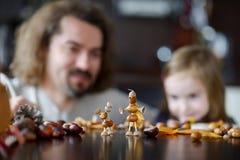Père et le sien enfant faisant des créatures de châtaignes Photographie stock libre de droits