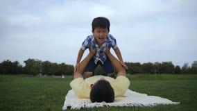 Père et loisirs asiatiques mignons d'enjoiyng de fils dehors banque de vidéos
