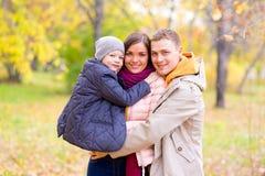 Père et mère avec le jeune fils sur des mains Autumn Park Photos libres de droits