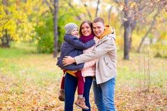 Père et mère avec le jeune fils sur des mains Autumn Park Image libre de droits
