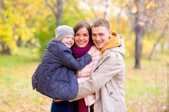 Père et mère avec le jeune fils sur des mains Autumn Park Photo libre de droits