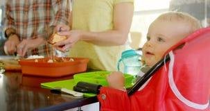 Père et mère préparant le petit déjeuner pour leur bébé garçon 4k banque de vidéos