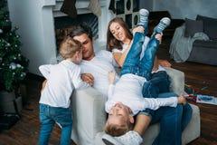 Père et mère se trouvant sur le sofa et jouant avec deux petits fils photo libre de droits