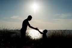 Père et petit fils contre le contexte du coucher du soleil de mer Photos stock