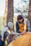 père et petit fils mignon mettant vers le haut de la tente images stock