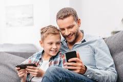 Père et petit fils s'asseyant sur le divan dans le salon photos stock