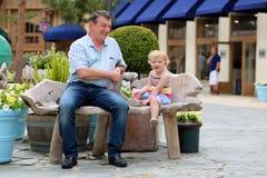 Père et petite fille détendant dans la ville Photo stock