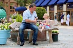 Père et petite fille détendant dans la ville Photos stock