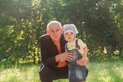 Père et petite-fille souriant à l'extérieur Photo stock