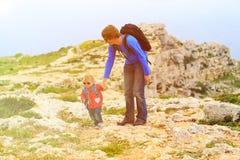 Père et petite fille trimardant en montagnes Photographie stock