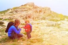 Père et petite fille trimardant en montagnes Images stock