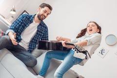 Père et peu de fille de fille à la maison faisant le concert pour le père image stock