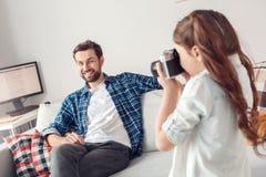 Père et peu de fille de fille à la maison prenant des photos de père se reposant sur le sourire de sofa joyeux photos stock