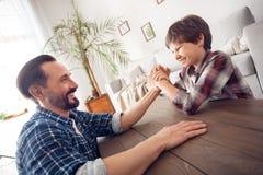 Père et peu de fils à la maison s'asseyant à la concurrence de bras de fer de table regardant l'un l'autre joyeux photos stock