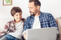 Père et peu de fils à la maison s'asseyant sur le sofa utilisant le plan rapproché joyeux d'ordinateur portable photographie stock libre de droits