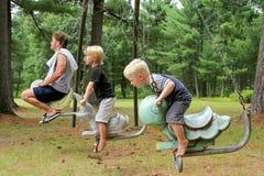 Père et ses enfants en bas âge montant des oscillations de planeur de terrain de jeu de vintage Photos libres de droits