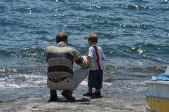 Père et soleil à un lac Photos libres de droits