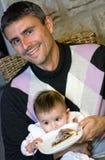 Père et son descendant essayant de manger Photographie stock