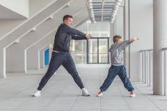 Père et son fils ou peu de garçon étirant des bras ensemble photos stock
