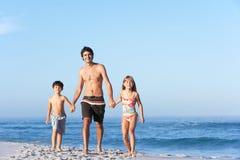 Père exécutant avec des enfants le long de plage sablonneuse photo stock