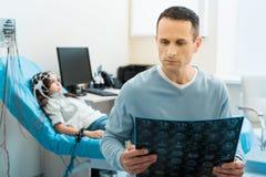 Père examinant des résultats de CT de sa fille Photos stock